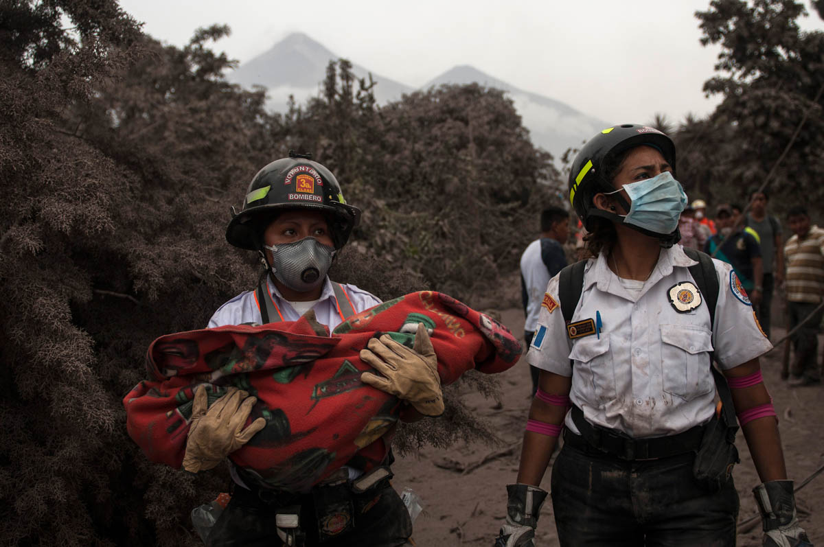 A firefighter carries the body of a child recovered near the Fuego volcano in Escuintla, Guatemala. [Oliver de Ros/AP Photo]