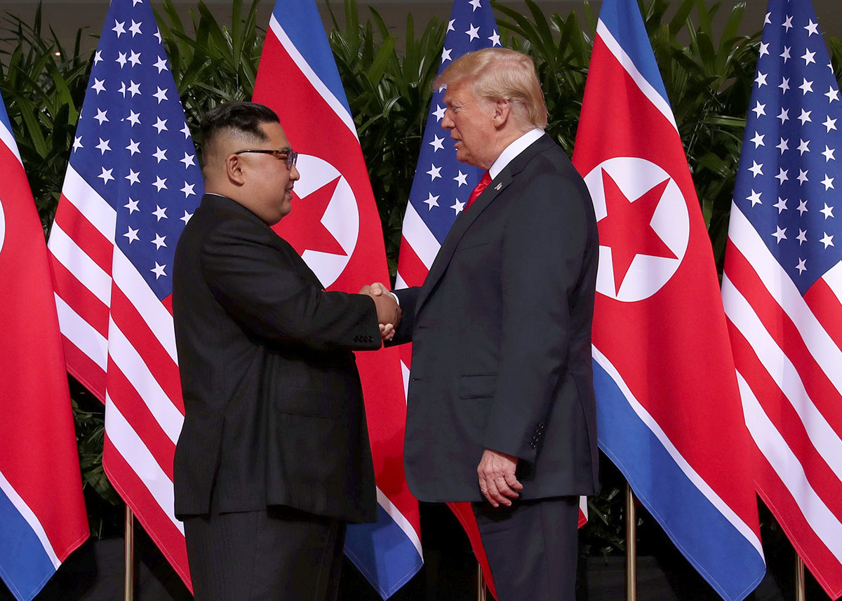 US President Donald Trump shakes hands with North Korean leader Kim Jong-un at the Capella Hotel on Sentosa island in Singapore. [Jonathan Ernst/Reuters]