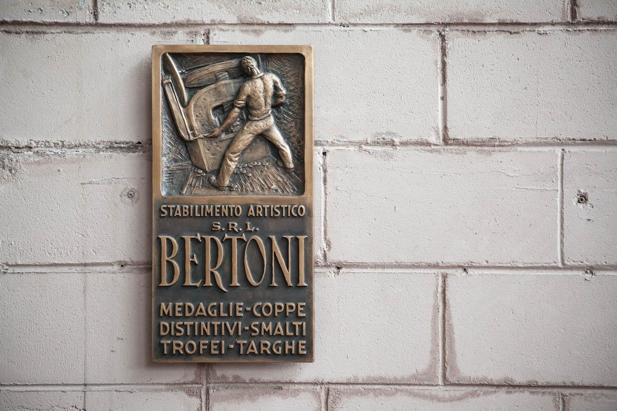 The historic brass emblem of Paderno Dugnano-based company GDE Bertoni which was established in Milan by Eugenio Losa in 1938. [Paolo Vezzoli/Al Jazeera]