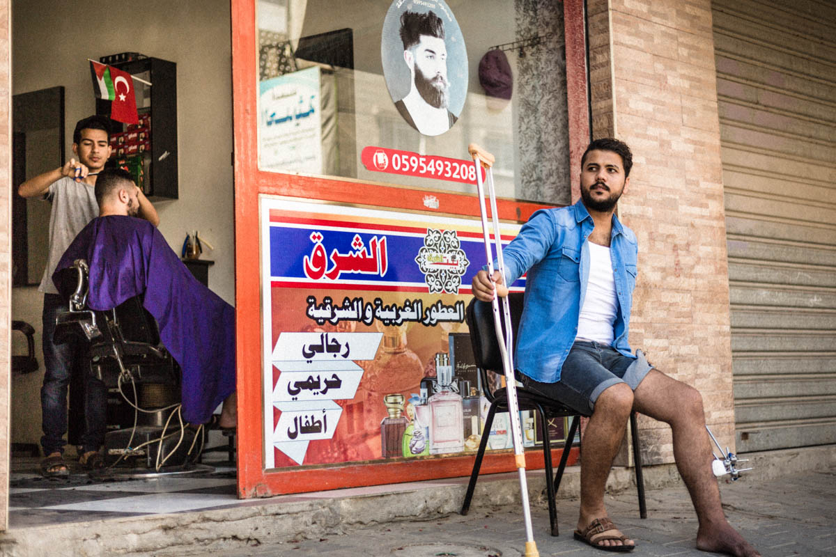 Mahmoud's young assistant has been running the barbershop alone. The business has lost many clients. Doctors have forbidden Mahmoud to work. His standing job may compromise his recovery. He still goes to his barbershop to lend a hand to his assistant and try to bring his customers back. [Alyona Synenko/ICRC]
