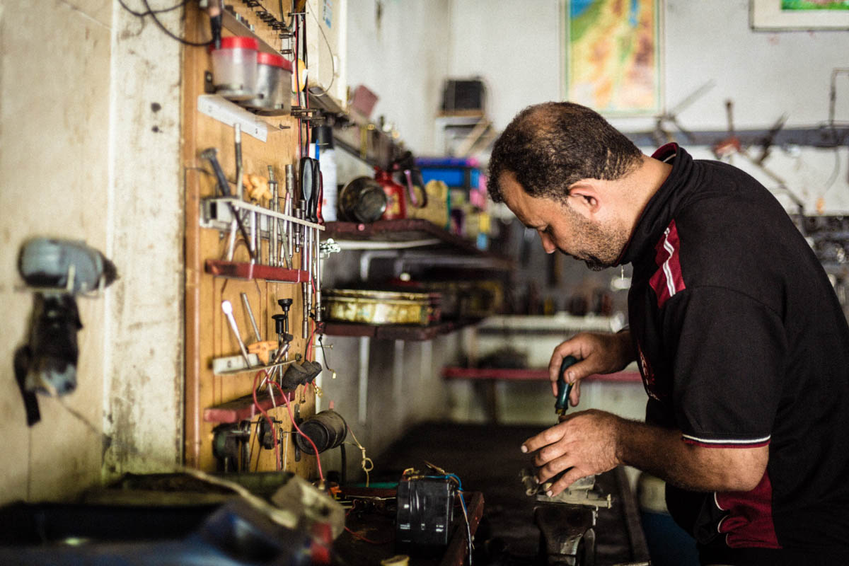 Raad, Baha's brother, is now running the mechanic workshop alone, while caring for his brother and trying to cover all the medical expenses. [Alyona Synenko/ICRC]