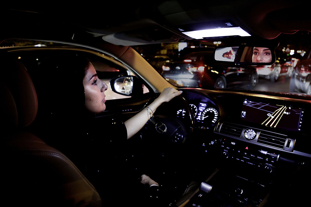 Hessah al-Ajaji drives her car down the capital's busy Tahlia Street after midnight for the first time in Riyadh, Saudi Arabia. [Nariman El-Mofty/AP Photo]