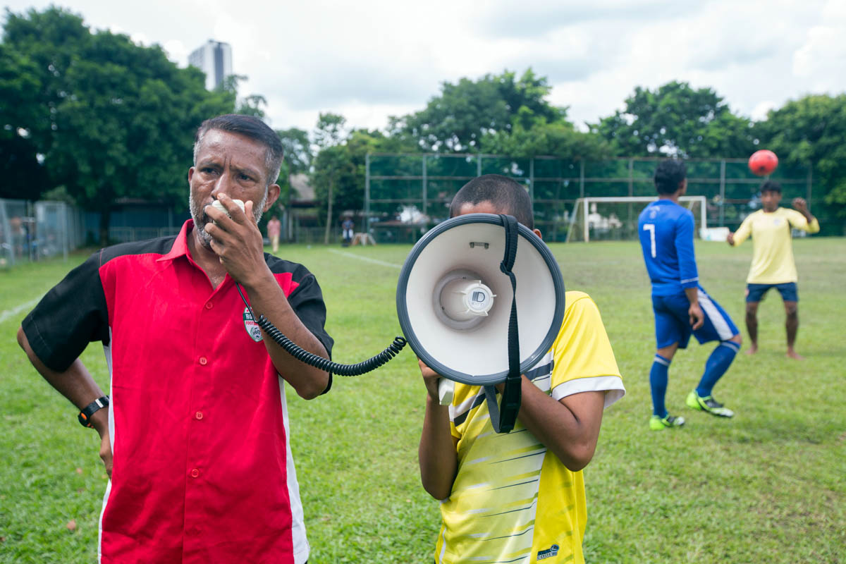 Dil Dar has been living in Malaysia for the last 20 years. He has been the team's coach since its creation three years ago and is seen gathering his team for last-minute instructions. [Alexandra Radu/Al Jazeera]