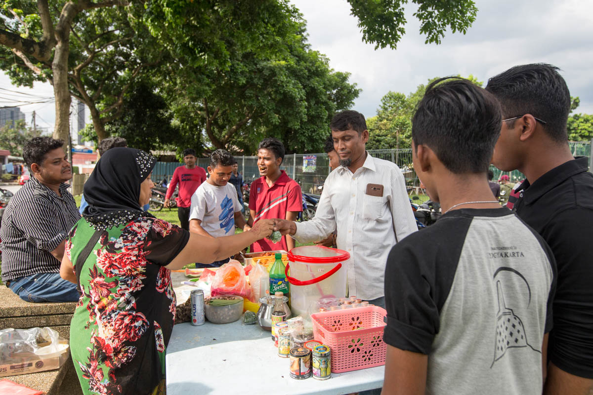 Fatimah cooks and sells food at every football event. Her husband plays in one of the local teams. She arrived in Malaysia as a child 30 years ago and has a family of six in the country. At every football event, she earns around MYR 50-70 ($12-16) from the food she sells. [Alexandra Radu/Al Jazeera]