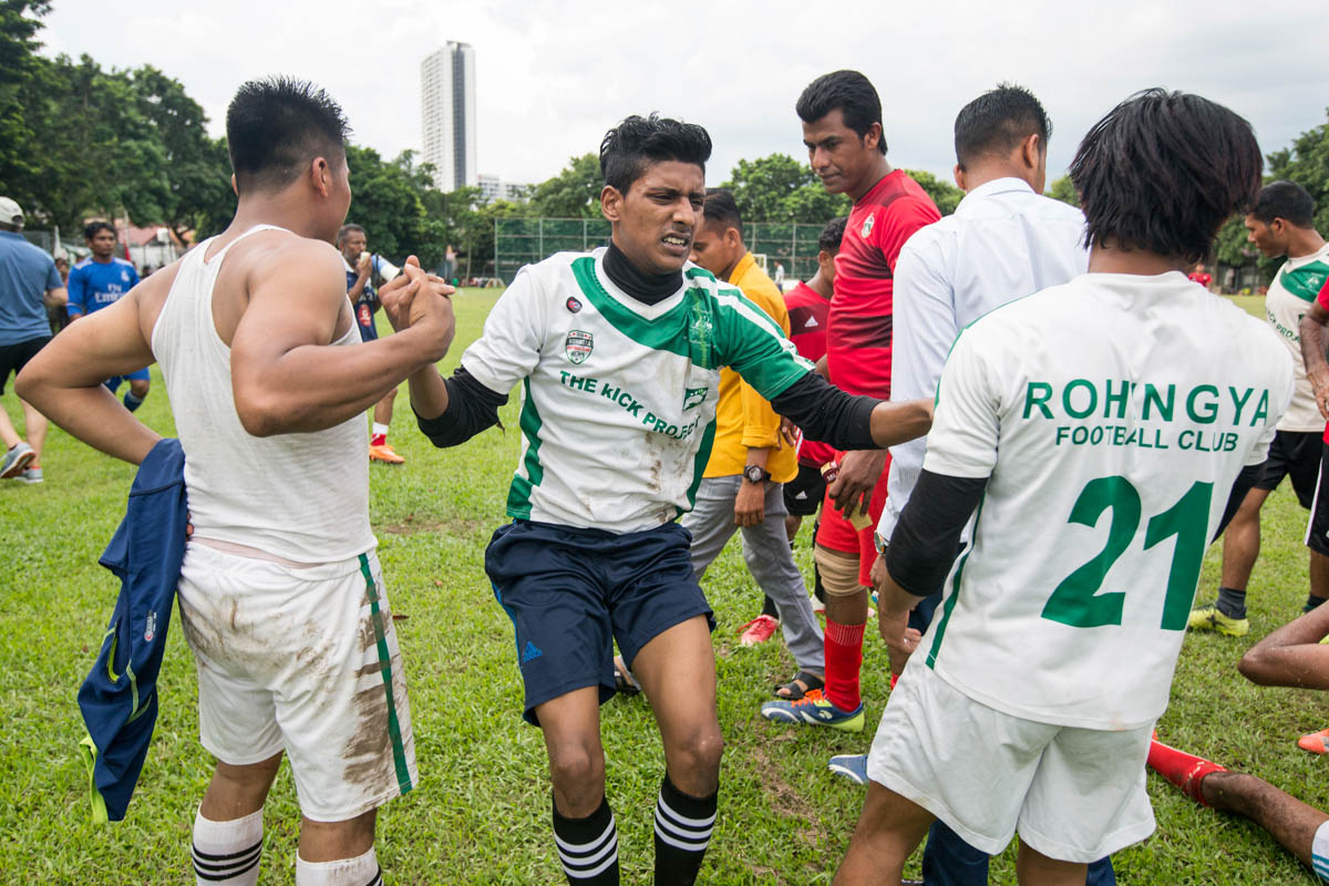 "Farouk Yusuf (C), 22, one of RFC's defenders, is lifted by his teammates after being injured during the match. Yusuf trains to be a professional footballer. He was born in Malaysia and went to a community school. ""In 2014, I received an email from FC Barcelona after I sent them a 30-second video of me playing. They said they were interested and wanted me to come to Barcelona for a one-month trial. If selected, they would train me for three months. Unfortunately, I do not have a passport so I couldn't go,"" said Yusuf. [Alexandra Radu/Al Jazeera]"