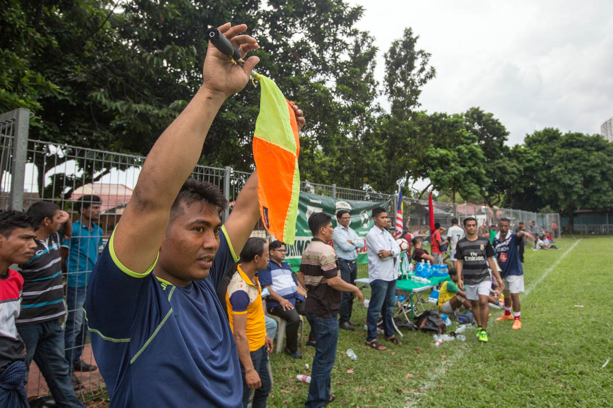 Abdullah, an RFC player, doubles up as a linesman in the second half of the match. He arrived in Malaysia in 2013 alone but managed to bring his family four years later. Abdullah said he was fortunate to work as an electrician and car mechanic, skills that he acquired in Myanmar. [Alexandra Radu/Al Jazeera]