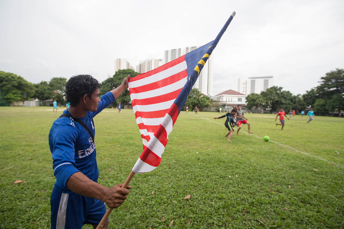 A Rohingya man unfolds the Malaysian flag during the warmup session. A large number of Rohingya have arrived in Malaysia during the last 30 years. They have families with them now but their children are stateless and many are undocumented in the country they now call home. This hinders access to education, healthcare, work and travel. [Alexandra Radu/Al Jazeera]