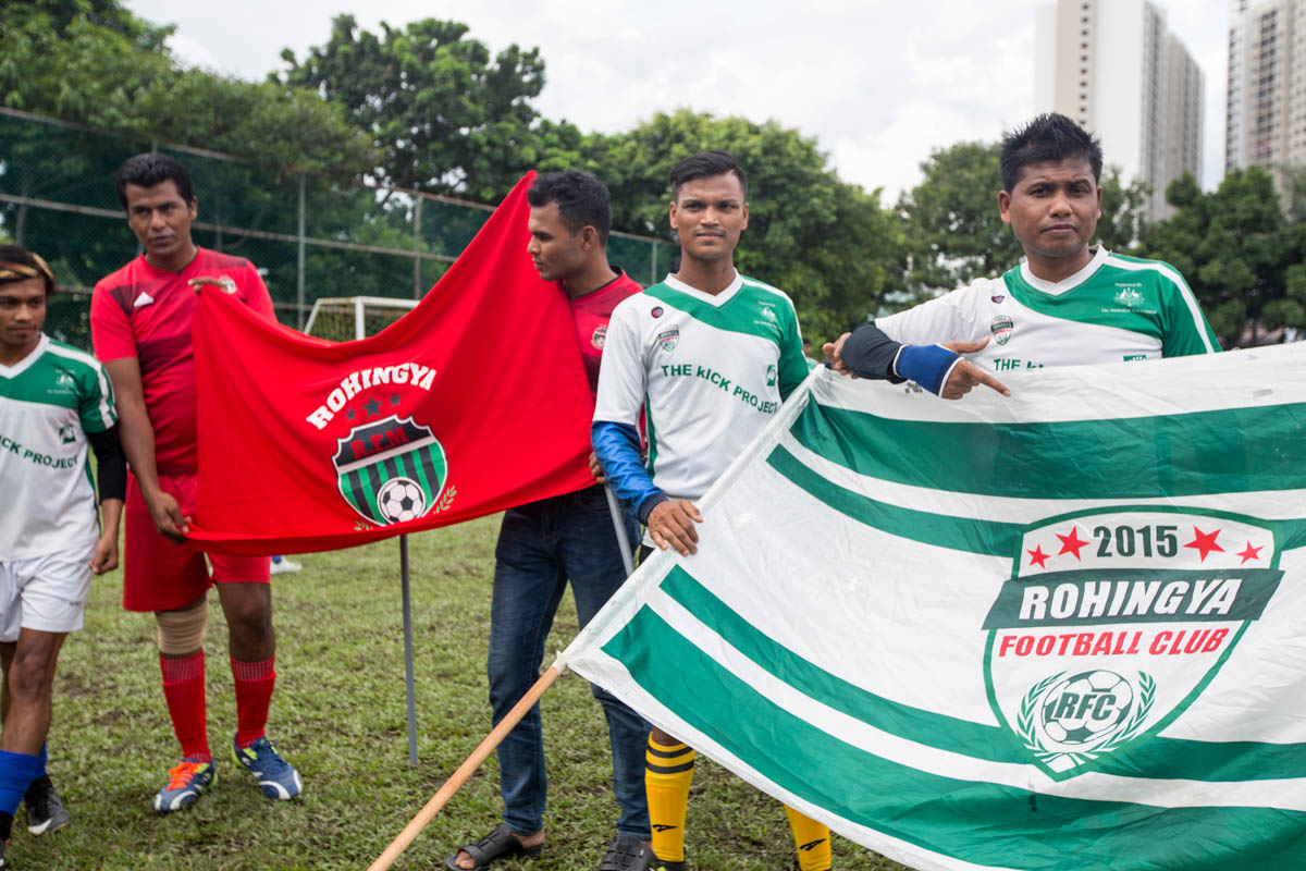 Team members hold their respective club flags before kick-off. Some of the Rohingya football players aim to become professional players but all of them have various jobs to support their families. [Alexandra Radu/Al Jazeera]