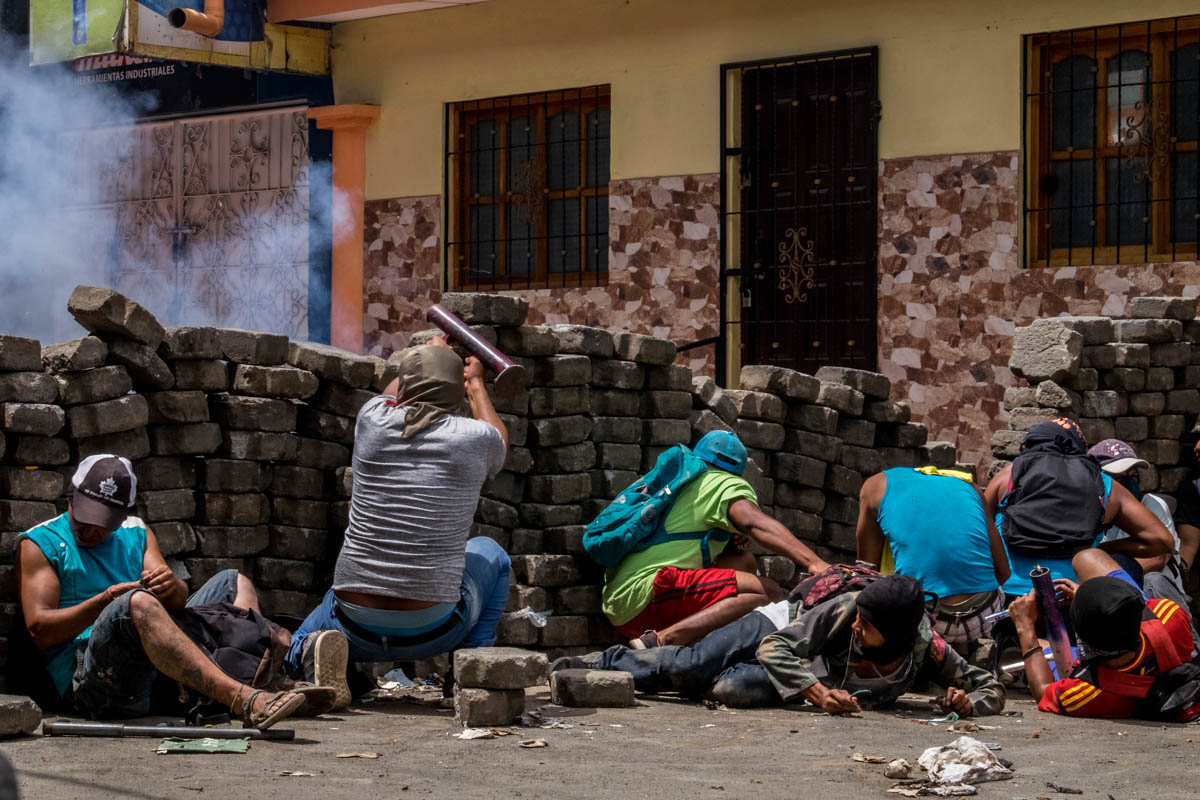 Citizens of Masaya, Nicaragua, react to the bullets fired by police as they shoot back with self-made 'mortars' in one of the hundreds of barricades erected in the city. [Javier Bauluz/Al Jazeera]