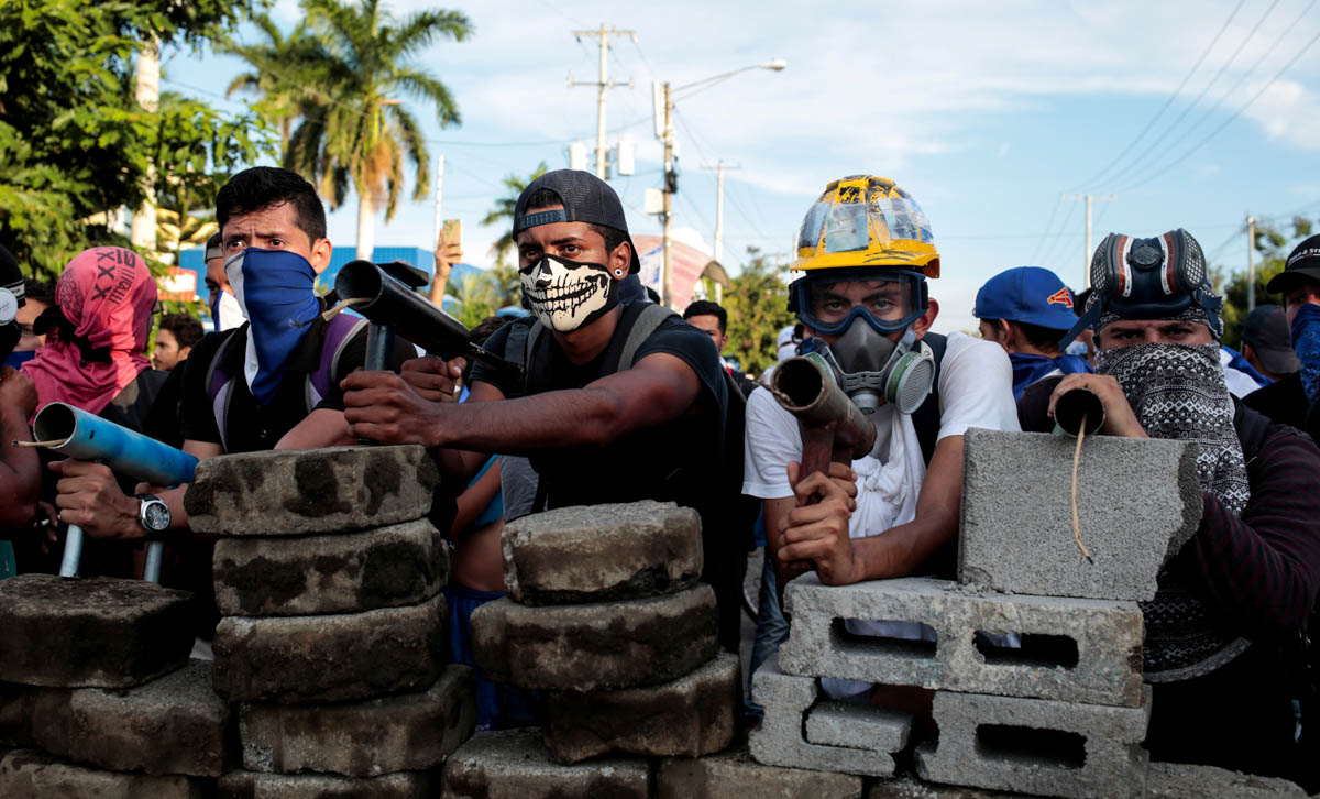 Demonstrators stand behind a barricade during clashes with riot police in a protest against Nicaragua's President Daniel Ortega's government in Managua, Nicaragua. [Oswaldo Rivas/Reuters]