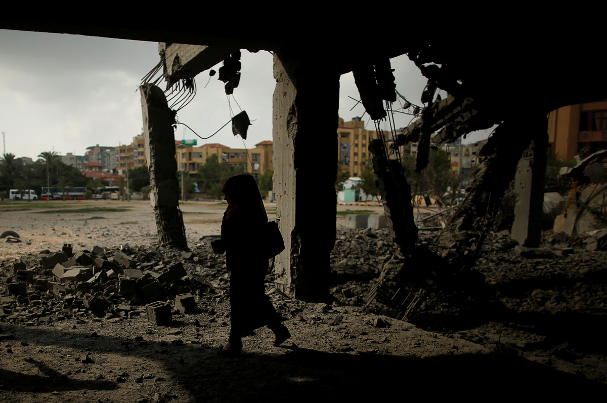 A Palestinian woman walks past a building that was destroyed by the bombing. A ceasefire agreement between Hamas and Israel was reached through international and regional mediation efforts. [Suhaib Salem/Reuters]