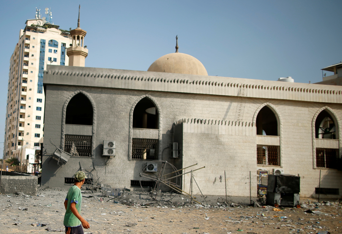 A Palestinian walks past Sheikh Zayed mosque damaged by Israeli air raids. The Israeli military said it had warned residents to evacuate prior to the attack. [Suhaib Salem/Reuters]