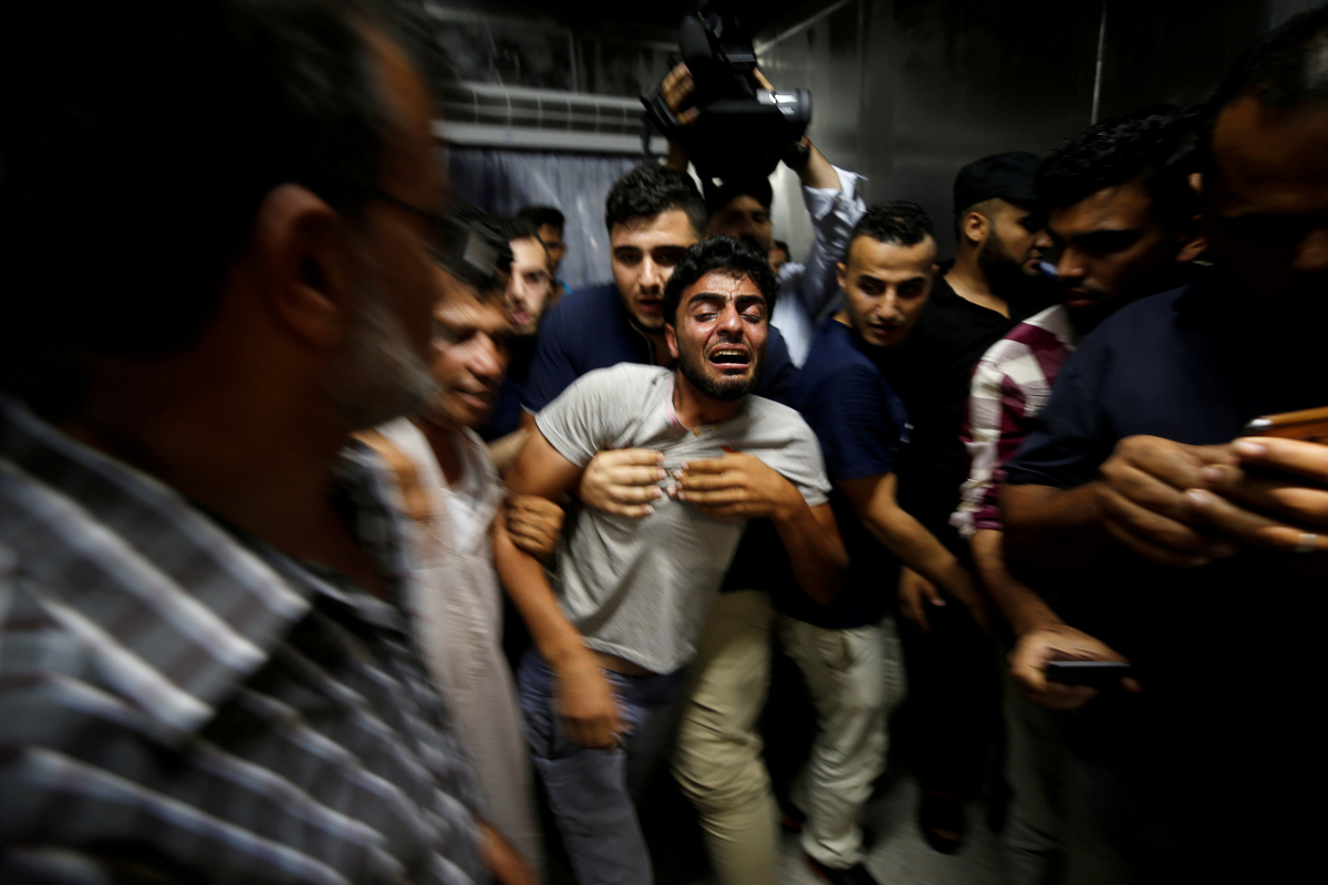 The brother of a Palestinian teenager who was killed reacts to the news of his brother's death. According to Palestinian health officials, at least two teenagers in the Gaza Strip have been killed by air raids carried out by the Israeli army. [Mohammed Salem/Reuters]