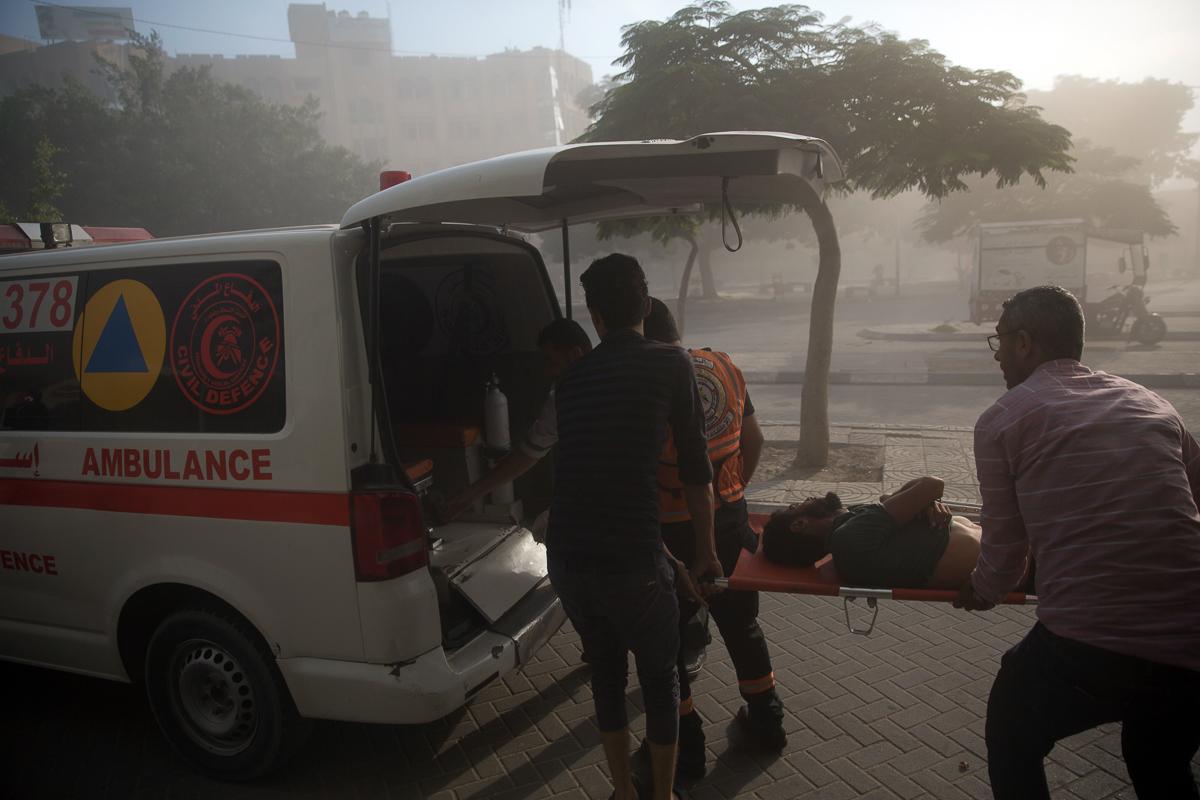 Medics evacuate a wounded Palestinian following an Israeli air raid. [Khalil Hamra/AP Photo]