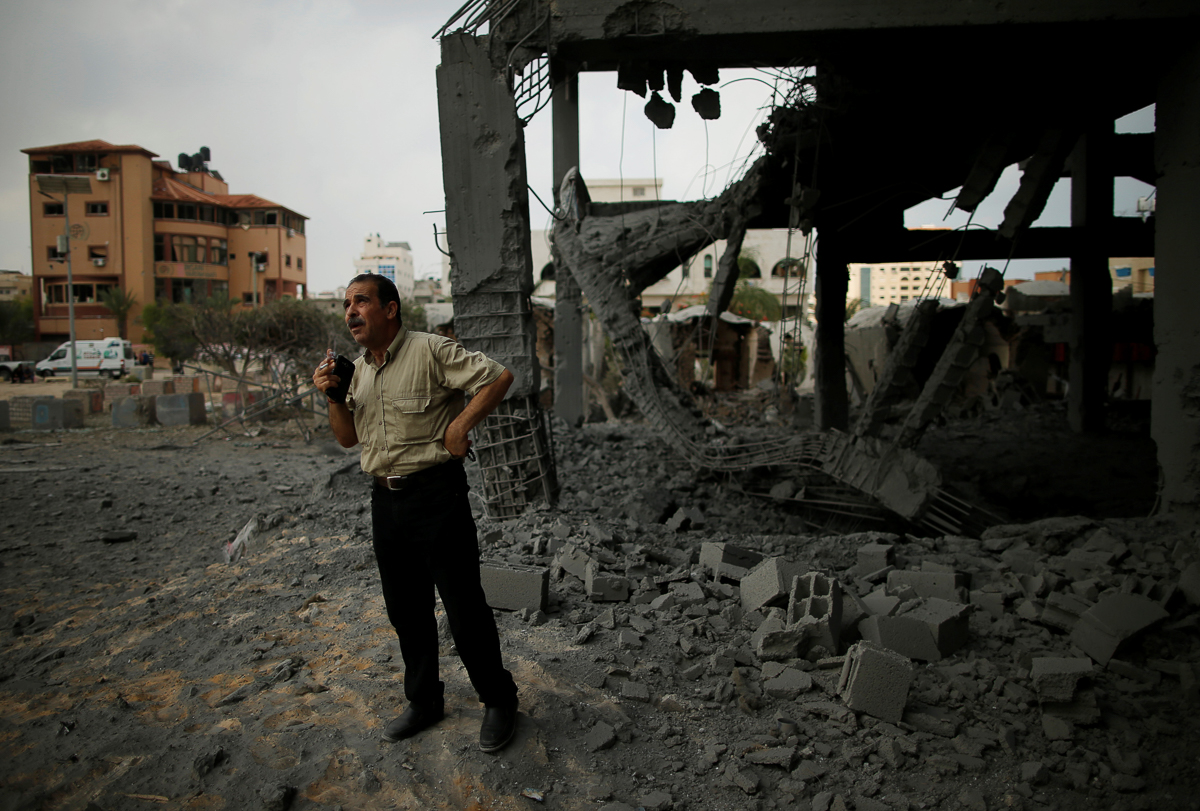 A Palestinian man looks at a building destroyed by Israeli attacks. Israeli military confirmed it targeted a 'high-rise building'. [Suhaib Salem/Reuters]