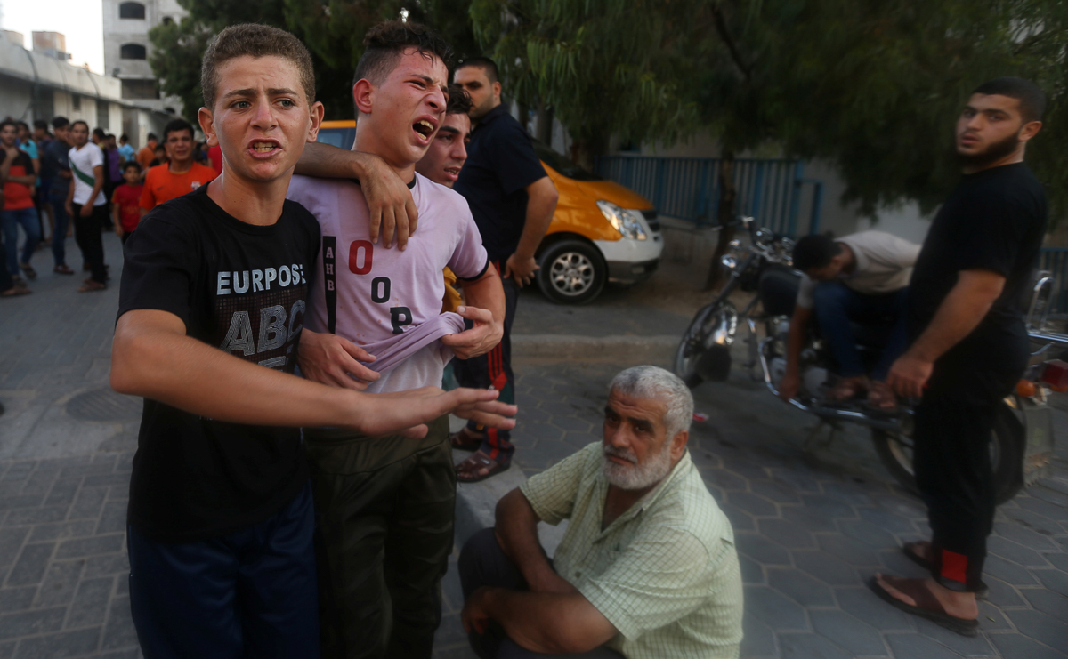 Residents react after learning of one their relatives was killed by an Israeli attack. According to witnesses, the two teenagers killed were playing on the roof of a semi-abandoned building. [Ibraheem Abu Mustafa/Reuters]