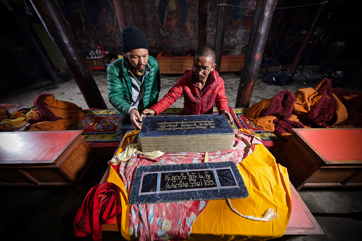 Chime Gurung, a Buddhist monk, shows Tashi Bista an ancient manuscript written in pure gold at a monastery in Lo Manthang, Nepal. Its sister book is believed to have been stolen from a stupa. This manual was saved. [Steve Chao/Al Jazeera]