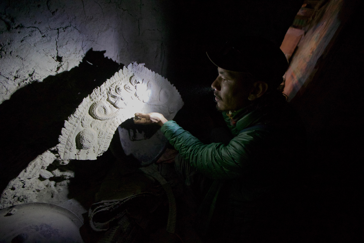 Tashi Bista examines ancient armour discarded in a hallway in a monastery built into a cliff in Mustang, Nepal. Tashi, a local Mustang resident, has fought for years to stop the theft of antiquities from his region.  The piece lies beside 14th century shields and body armour. [Steve Chao/Al Jazeera]