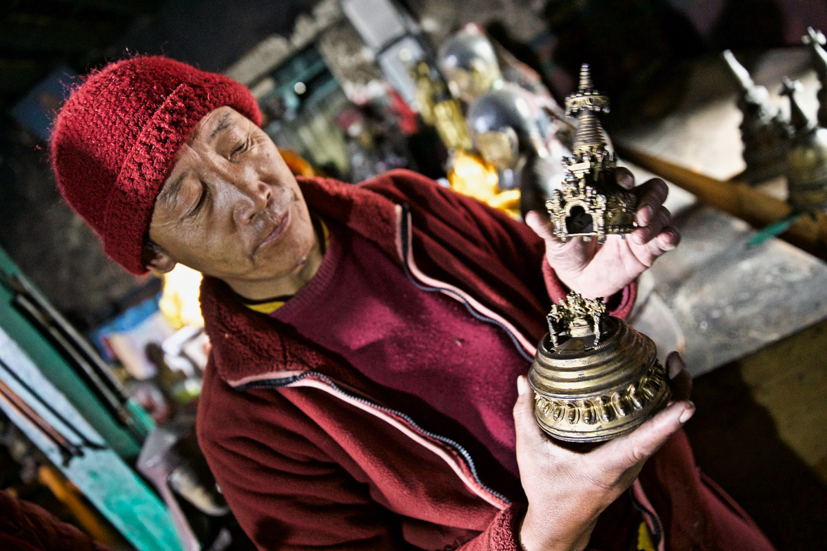 A monk reveals intricately crafted gods hidden inside a copper stupa in Namygal Monastery in Mustang, Nepal. These rare idols are highly sought after by thieves, and the monastery has been forced to lock them away for safekeeping. [Steve Chao/Al Jazeera]
