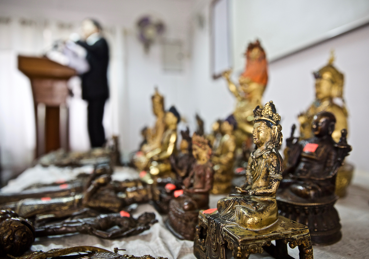 Authorities in Nepal hold a press conference displaying more than 100 antiquities seized in a raid of three antique shops in Kathmandu in May. The raid was initiated by information provided by 101 East's investigation into illegal antique sales. [Steve Chao/Al Jazeera]