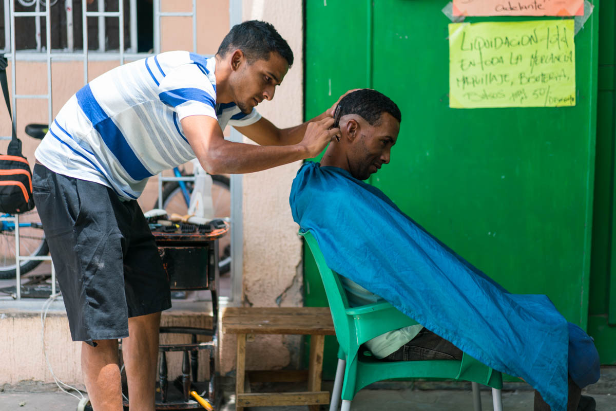 Luis* gives haircuts for 1,000 Colombian pesos, less than $1 USD, next to the Simon Bolivar Bridge near Cucuta, Colombia, bordering Venezuela. His wife, who is pregnant, is in Venezuela. He said he is earning money to buy diapers in Colombia to bring home. [Iris V. Ebert/IRC]