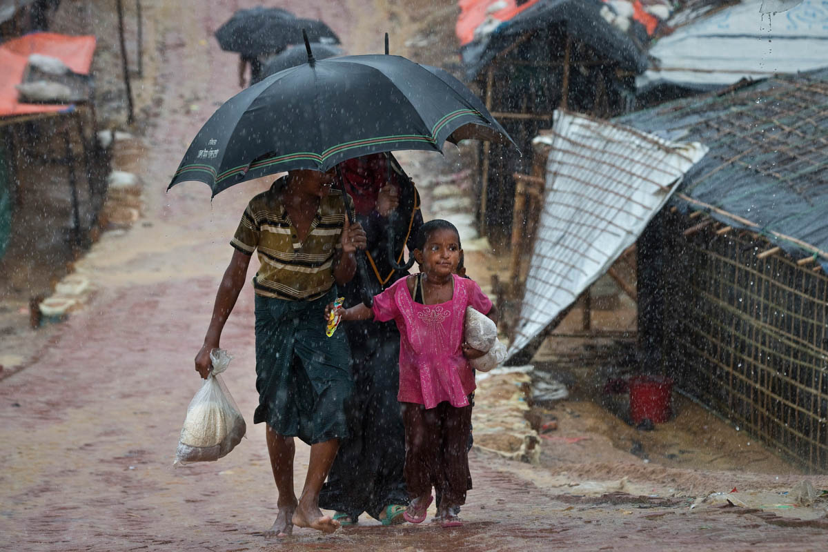 Rohingya refugees shield themselves from the rain in Balukhali, Camp 10. Daily landslides are expected, and agencies have put in place a mass casualty plan, with an estimated 200,000 people at risk. [Siegfried Modola/Al Jazeera]