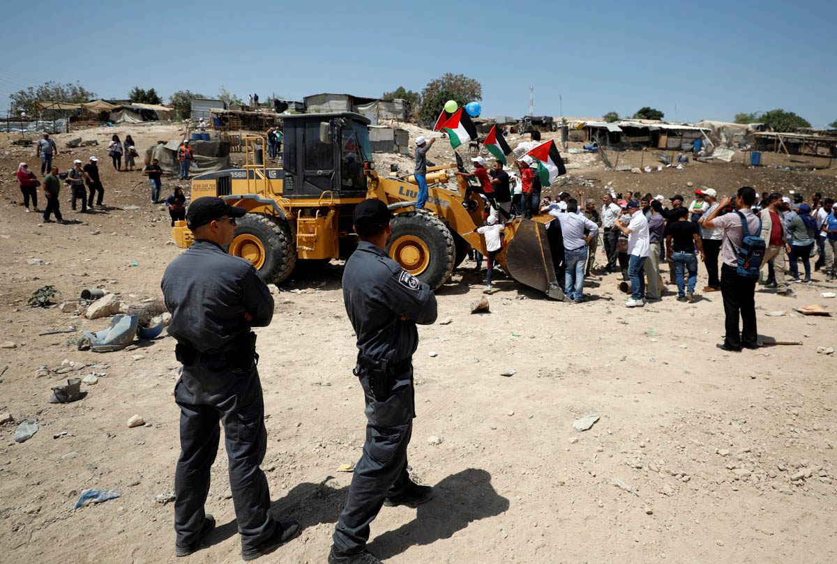 Those present at the scene congregated around the bulldozer in an attempt to prevent it from beginning the demolition of the village. [Mohamad Torokman/Reuters]