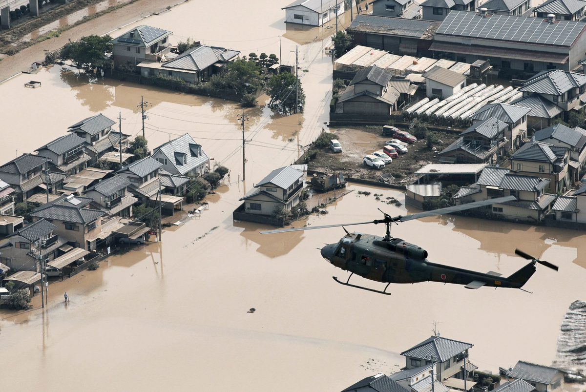 A helicopter flies over Mabi town in Kurashiki, Okayama Prefecture. [Kyodo via Reuters]