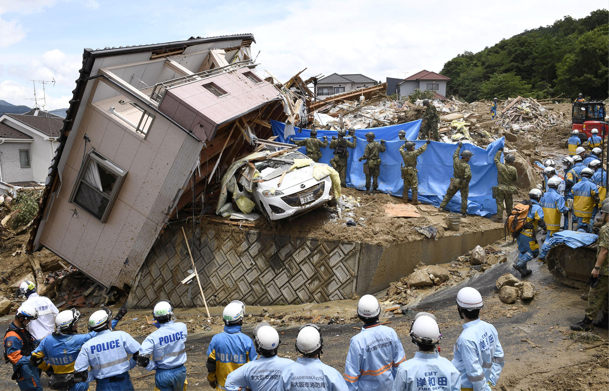 Rescue workers look for missing people in a house damaged by heavy rain in Kumano, Hiroshima Prefecture. [Kyodo via Reuters]