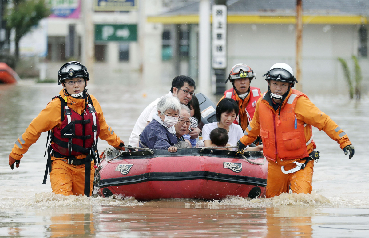 Residents rescued from a flooded area in Kurashiki, Okayama Prefecture. [Kyodo via Reuters]