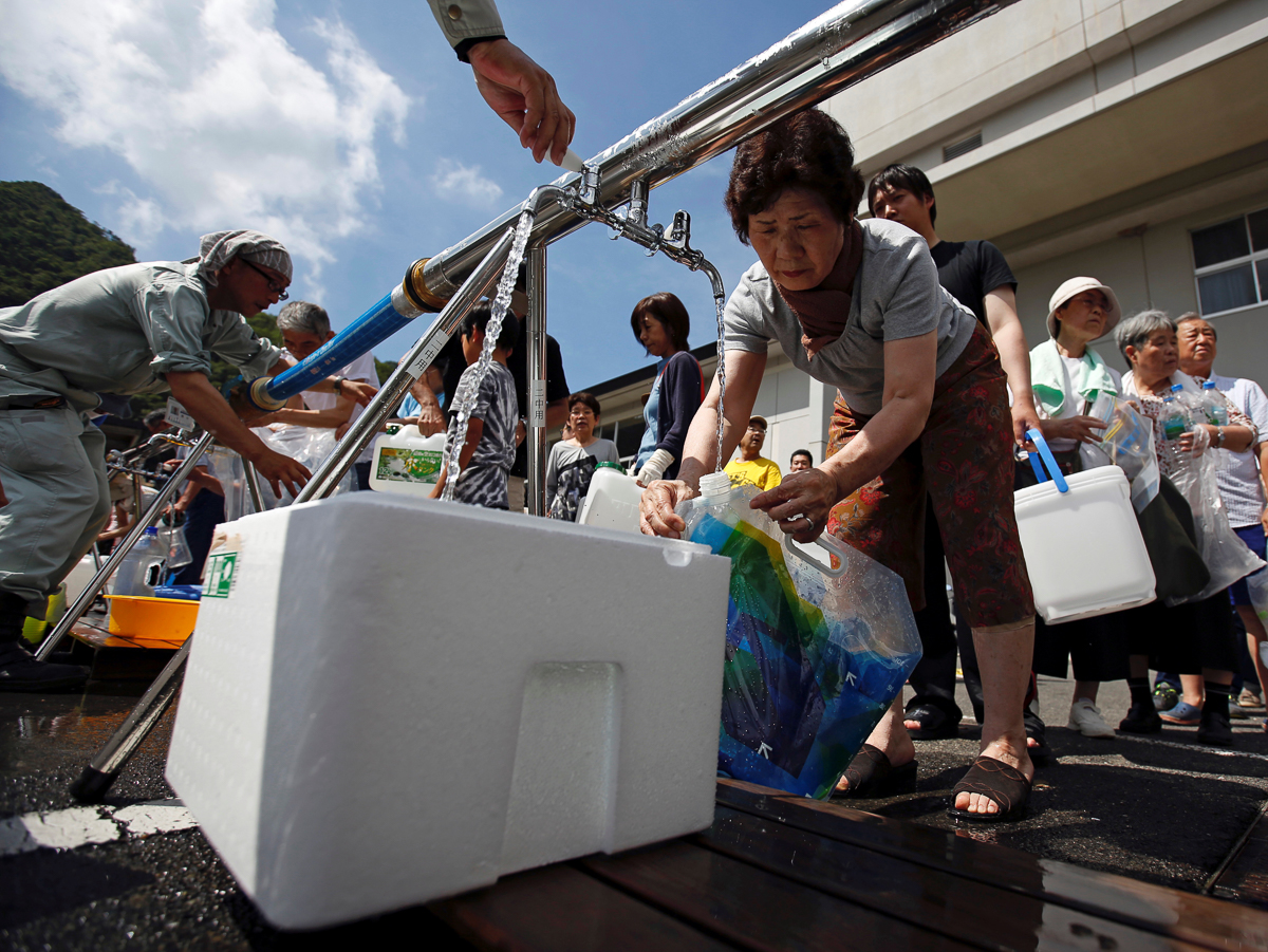 Residents receive emergency water supply at Mihara Daini junior high school, which is acting as an emergency water station, in Mihara, Hiroshima Prefecture. A new evacuation order went out on Tuesday in part of Hiroshima Prefecture, after a river blocked by debris overflowed its banks, affecting 23,000 people. [Issei Kato/Reuters]