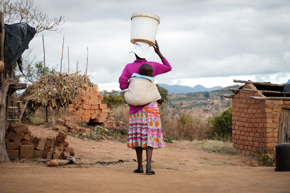 Patricia Mukarakati, 35, carries a bucket on her head with her baby strapped to her back at her homestead in rural Mutasa district, Manicaland, Zimbabwe. [Annie Mpulame/UNICEF]
