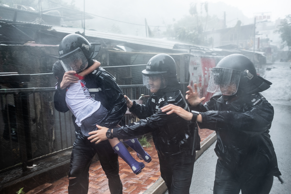 Police officers carry a girl out of a collapsed school in Hong Kong. [Lam Yik Fei/Getty Images]