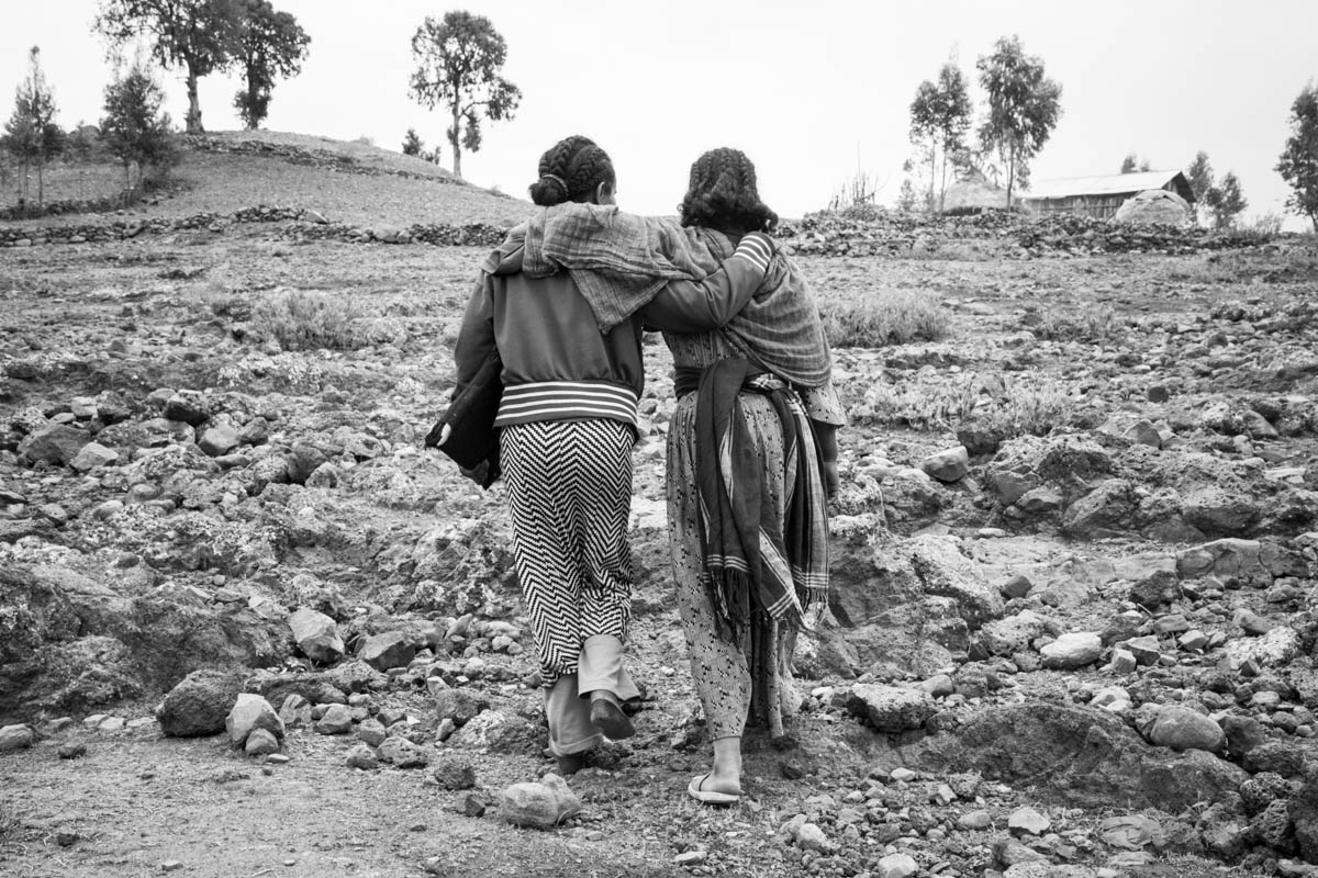 "Eniyat leans on her sister's shoulder as they walk to their home in the hills of Selamaya, a village in the highlands of North Gondar. Eniyat needs her sister's help with the daily 30-minute hike from school. Girls with impairments are vulnerable to abuse, as Eniyat puts it: ""It is not like we can see our attacker."" [Nathalie Bertrams/Al Jazeera]"