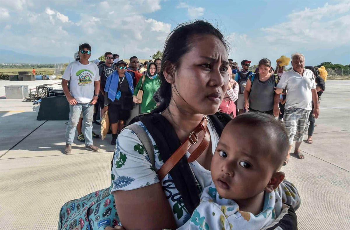 People affected by the earthquake and tsunami wait to be evacuated on an air force plane in Palu. [Muhammad Adimaja/Antara Foto/Reuters]