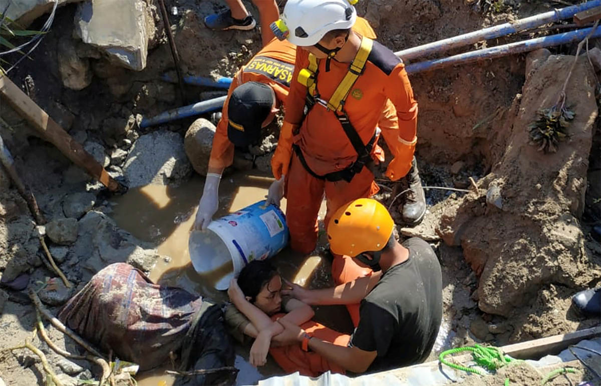 Search and rescue workers help a person trapped in rubble following the earthquake in Palu. [Darwin Fatir/Antara Foto/Reuters]