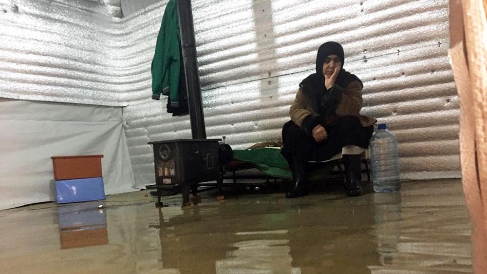 Syrian refugees wading through knee-deep water in Lebanon ...