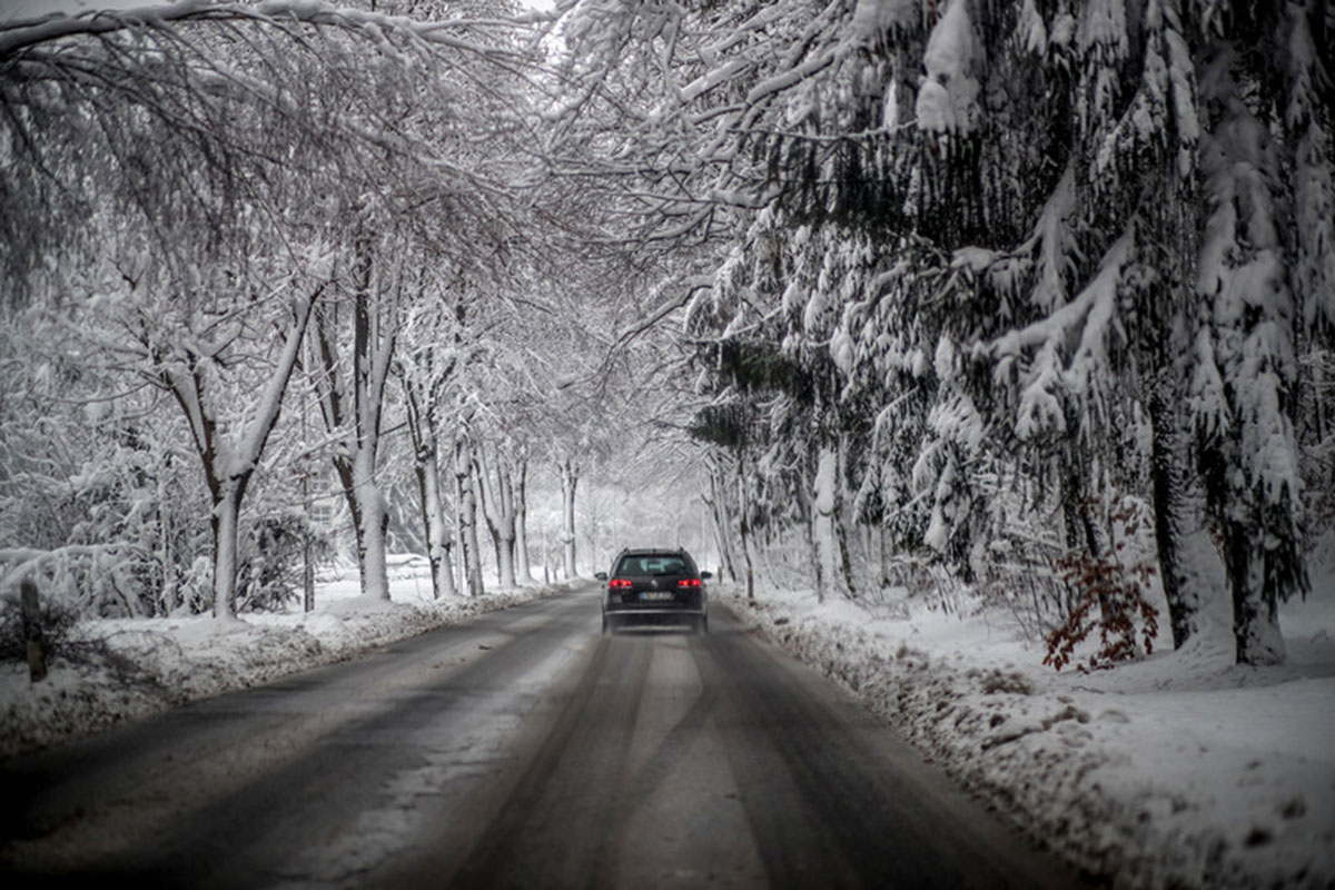 A car carefully navigates the roads under snow laden trees near Chemnitz, Sachsen, Germany. [Martin Divisek/EPA]