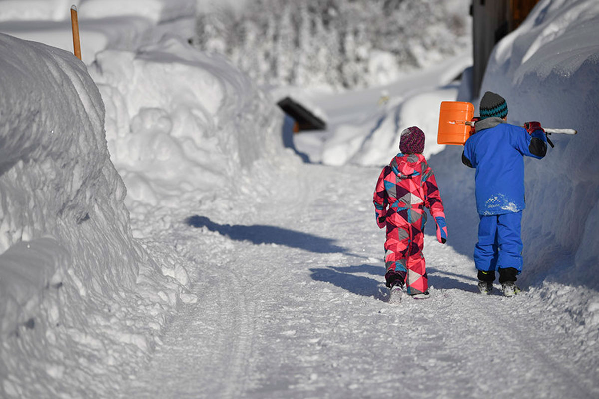 Children walk along a snow covered road in Gerold, Germany. [Philipp Guelland/EPA]