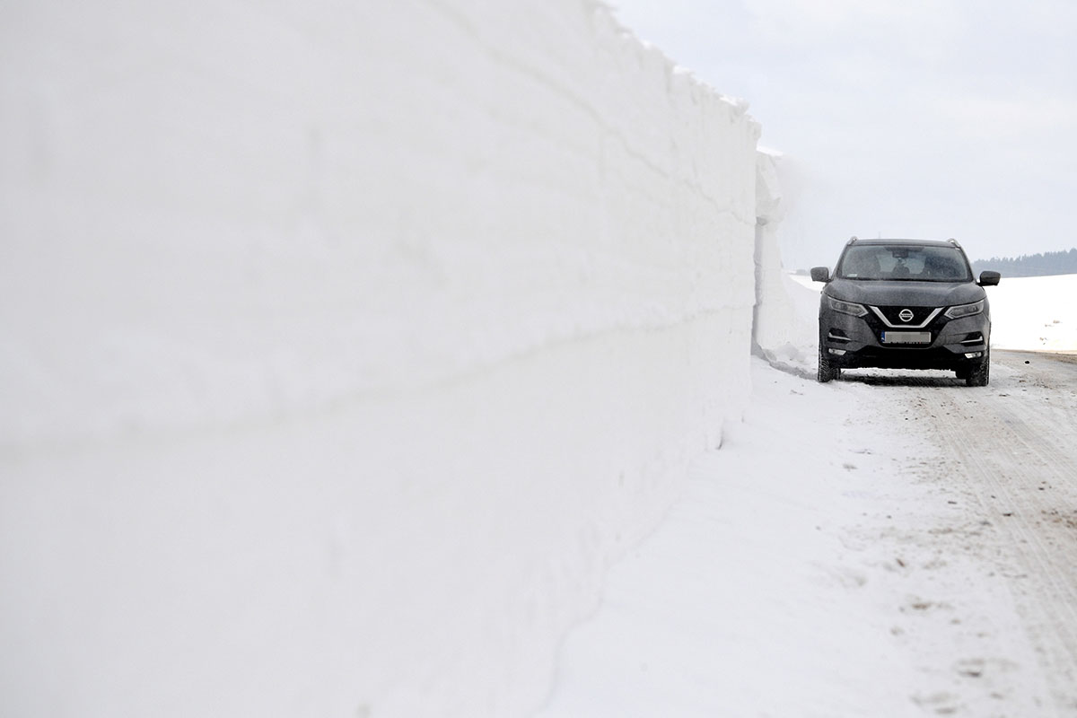 A car drives past a huge snow drift on a provincial road between Karlikow and Plonna  in southern Poland. [Darek Delmanowicz/EPA]