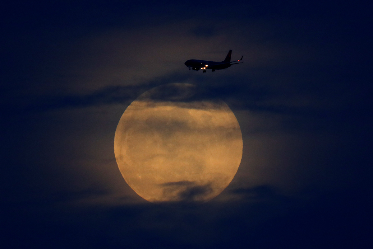 The moon rises between clouds as a landing commercial jet approaches the airport before the start of a total lunar eclipse that is being called a 'Super Blood Wolf Moon' in San Diego, California. [Mike Blake/Reuters]