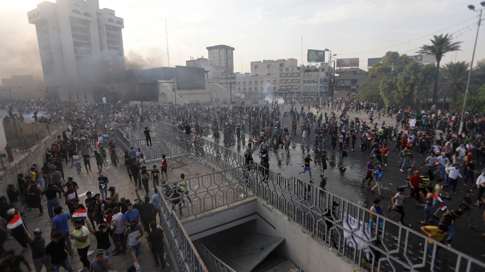 Demonstrators disperse as Iraqi Security forces use tear gas during a protest [Thaier al-Sudani/Reuters]