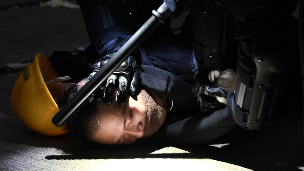 A man is detained by police during clashes in the Wanchai district in Hong Kong on October 1, 2019, as the city observes the National Day holiday to mark the 70th anniversary of communist China's fou