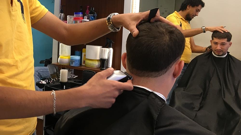 Ashrif gets a haircut at his local barber, like many Tunisians, he says he's lost faith in politicians but trusts Kais Saied  [Sofia Barbarani/Al Jazeera]