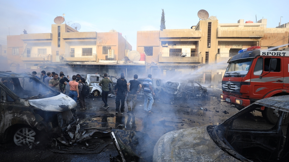 People gather at the site of a car bomb blast in Qamishli