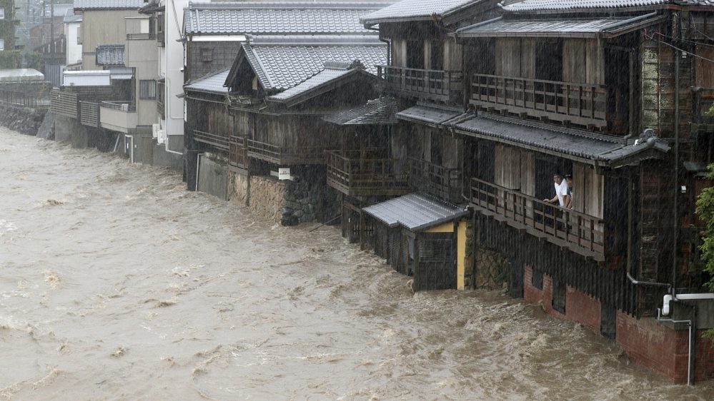 Men watch the swollen Isuzu River due to heavy rain caused by Typhoon Hagibis in Ise