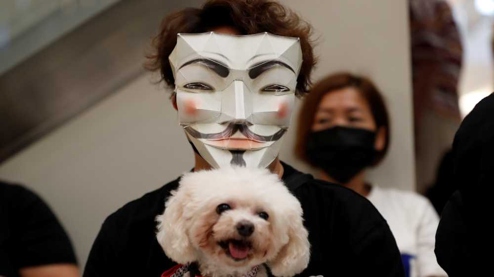 An anti-government protester holding a dog wears a mask during a demonstration at New Town Plaza shopping mall in Hong Kong