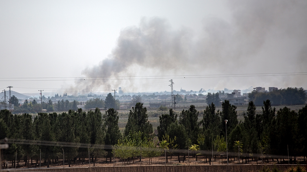 Smoke rises from the northeastern Syrian town of Tal Abyad  [Hosam Salem/Al Jazeera]