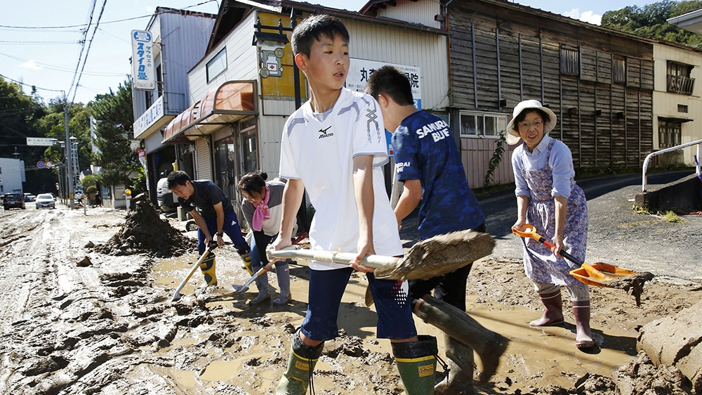 Schoolchildren and residents remove mud after flooding caused by Typhoon Hagibis in Marumori, Miyagi prefecture, Japan, October 13, 2019, in this photo taken by Kyodo. Mandatory credit Kyodo/via REUTE