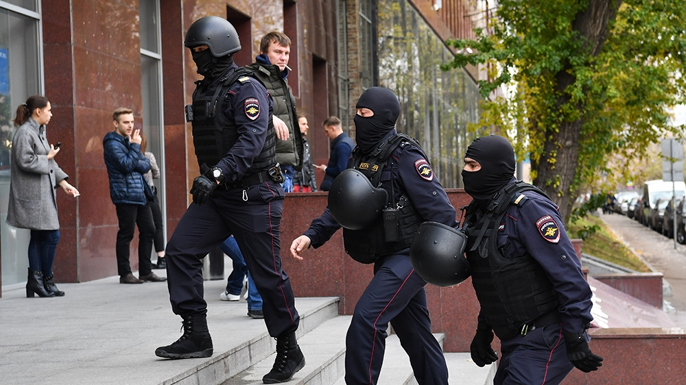Russian police officers walk to enter a business centre, which houses the office of opposition leader Alexei Navalny's Anti-Corruption Foundation (FBK), in Moscow on October 15, 2019. - Russian invest